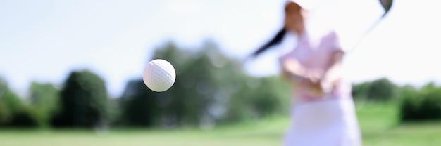 Golfball gegen hintergrund des schlagens der frau nahaufnahme