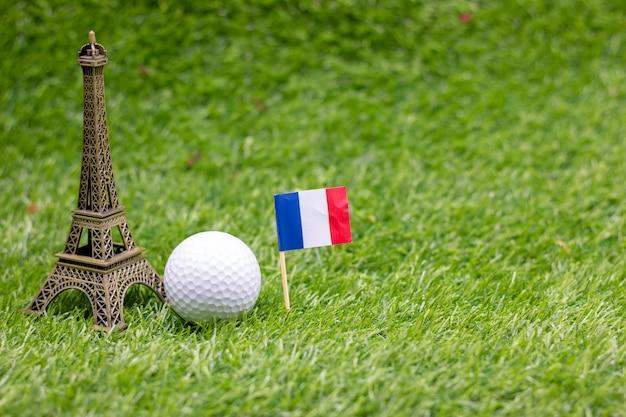 Golfball mit flagge von frankreich sind auf grünem gras.