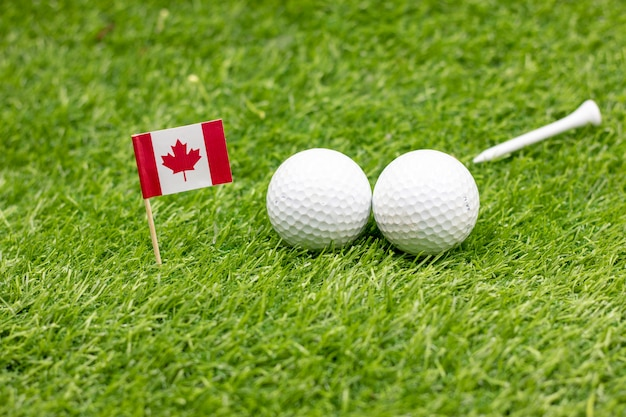 Golfball mit flagge von kanada auf grünem gras.