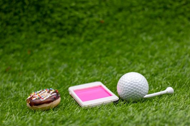 Golfball mit handy auf grünem gras.
