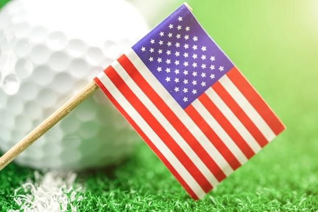 Golfball mit usa-flagge auf grünem rasen oder feld: populärster sport in der welt.