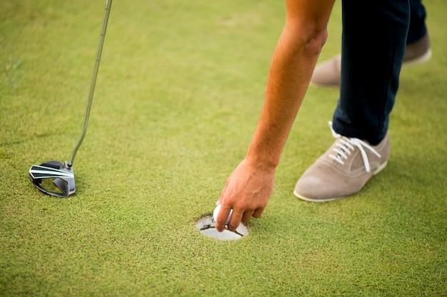 Golfball, putter und jungen beine auf grün