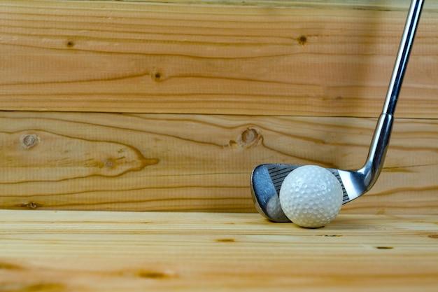 Golfball und golfclub auf holzfußboden