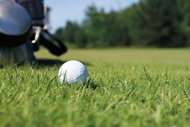 Golfball und pin sind spielbereit, auf einem grünen rasen mit natürlichem hintergrund platziert.