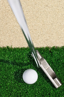 Golfball und putter auf grünem gras