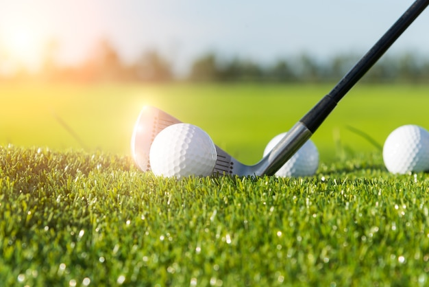 Golfclub und ball im gras und im sonnenuntergang