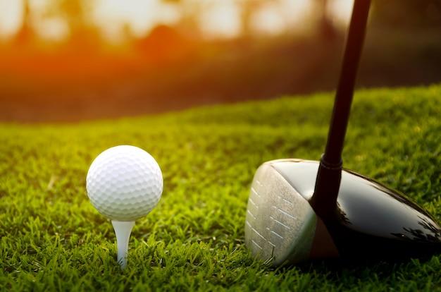 Golfclub und ball im gras zur sonnenuntergangzeit