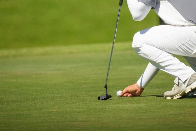 Golfer markiert seine position auf einem grün