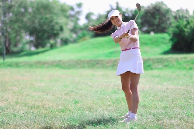 Golferin macht schlag mit golfschläger