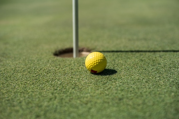 Golfplatz mit gelbem ball in der nähe des lochs
