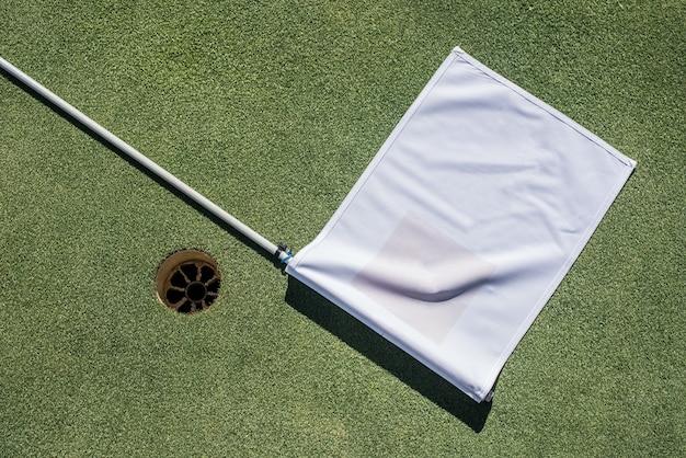 Golfplatz mit leerem loch und weißer flagge
