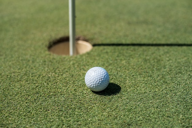 Golfplatz mit weißem ball in der nähe des lochs