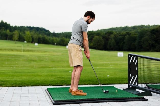 Golfprofi, der auf einem golffeld übt