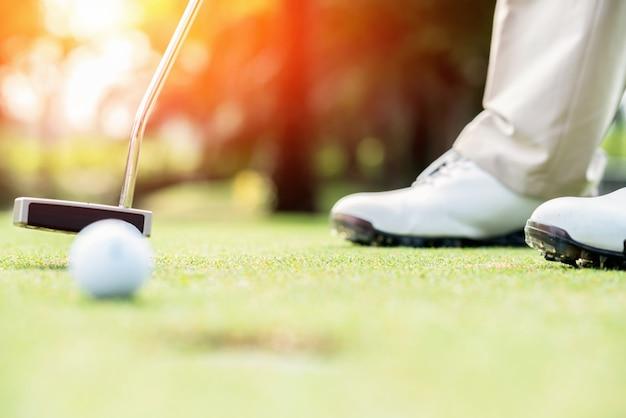 Golfspieler am schlagball des putting green in ein loch