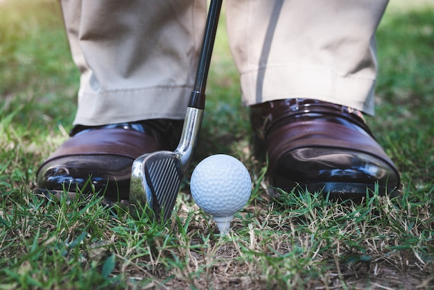 Golfspieler, der auf dem feld steht, um golf auf dem platzabschlag zu spielen