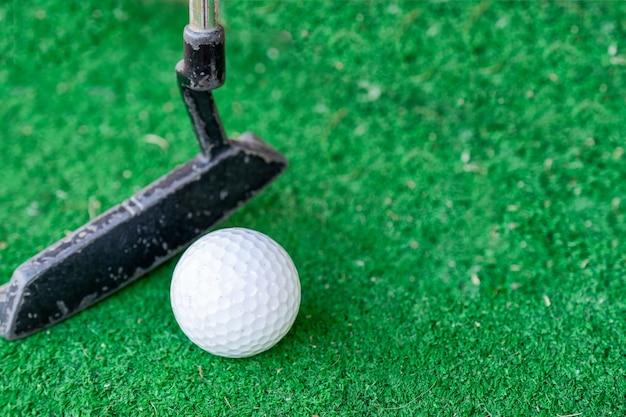 Golfspieler, der auf trainingsputt mit golfball sich vorbereitet