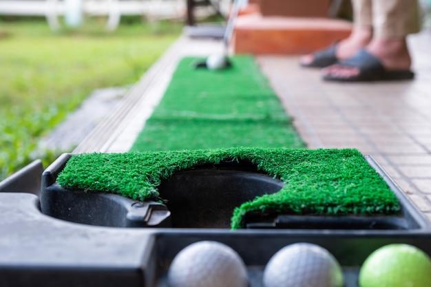 Golfspieler, der auf trainingsschlag mit golfball sich vorbereitet