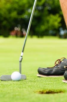 Golfspieler, der ball in loch einsetzt