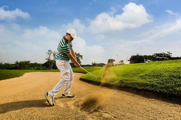 Golfspieler, der den ball auf dem sand schlägt. geschwindigkeiten ursache durch bewegung verschwommen