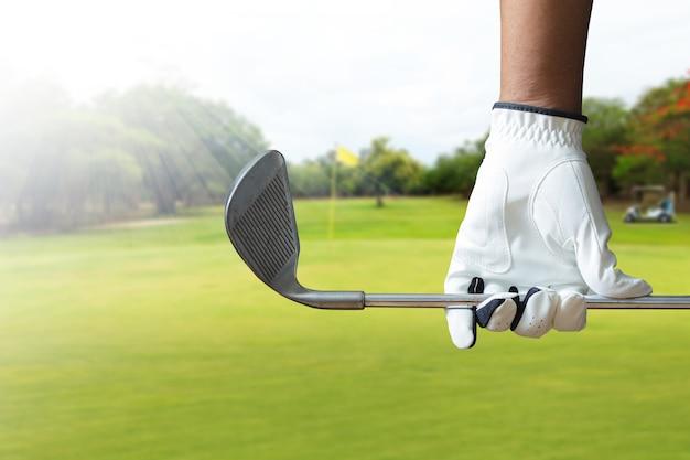 Golfspieler, der einen golfclub im golfplatz hält