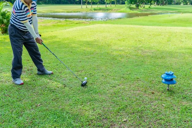 Golfspieler, der für ein schlagen durch fahrer vom t-stück in einem golfplatz sich vorbereitet.
