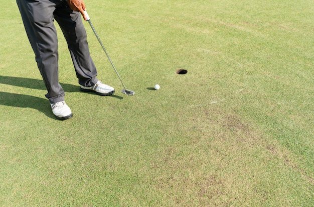 Golfspieler, der für einen schlag auf dem grün während des golfplatzes sich vorbereitet