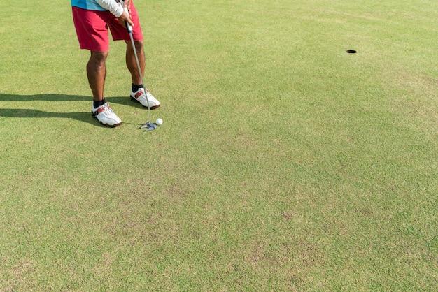 Golfspieler, der für einen schlag auf dem grün während des golfplatzes sich vorbereitet.