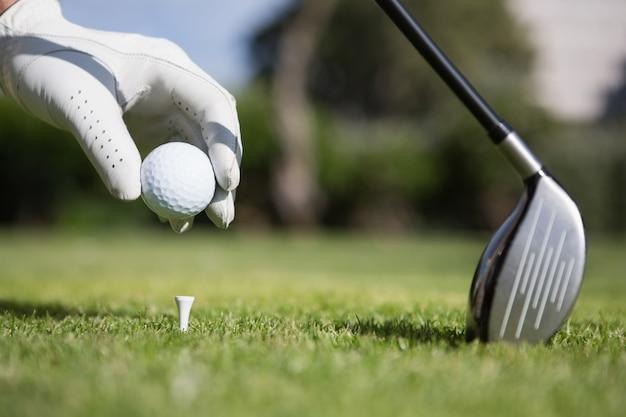 Golfspieler, der golfball auf t-stück setzt
