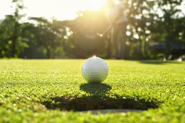Golfspieler, der golfball in loch setzt