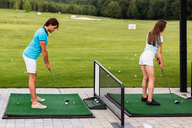 Golfspieler der hinteren ansicht, die schwingen üben