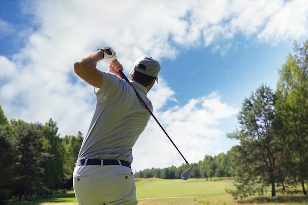 Golfspieler, der im sommerurlaub golf mit schläger auf kurs schlägt.