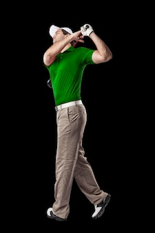 Golfspieler in einem grünen hemd, das eine schaukel nimmt, auf einem schwarzen hintergrund.