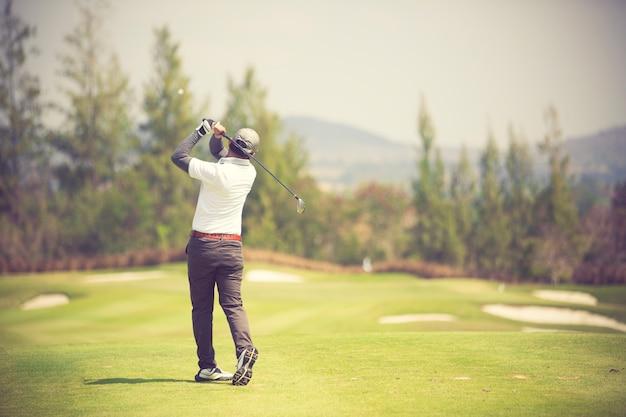 Golfspieler schlagen ausgedehnten golfplatz in der sommerweinlesefarbe