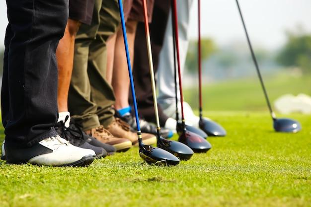 Golfspieler- und golftreiberkopf in folge auf grün