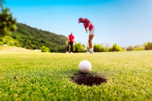 Golfspielerfokus, der golfball in das loch während des sonnenuntergangs, des gesunden und lebensstil-konzeptes setzt.