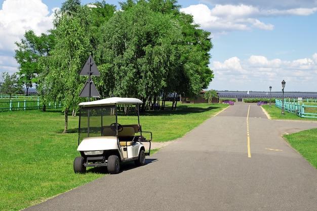 Golfwagen oder auto auf dem golfplatz, der an der parkstraße geparkt ist