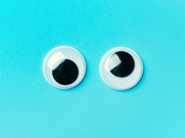 Googly augen auf blauem hintergrund. draufsicht oder flache lage. plastikspielzeugaugen auf türkisfarbenem hintergrund