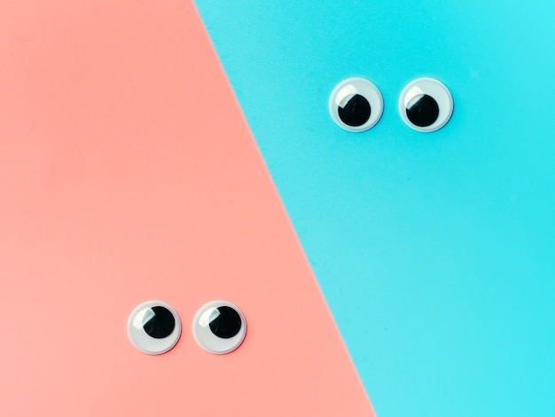 Googly augen auf blauem rosa hintergrund. draufsicht oder flache lage. plastikspielzeugaugen auf türkisfarbenem hintergrund