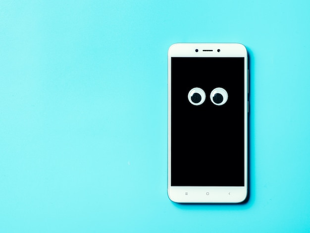 Googly augen auf smartphone-bildschirm über blauem hintergrund mit kopierraum übrig.