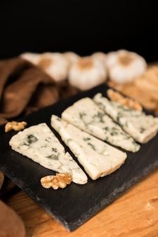 Gorgonzola-käsescheiben und -walnuss auf schwarzem stein