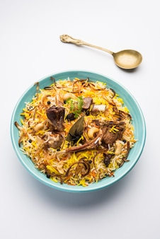 Gosht oder mutton biryani im restaurantstil serviert in einer schüssel mit raita und salan