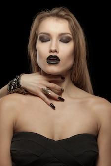 Gotische frau mit der hand des vampirs auf ihrem stutzen. halloween
