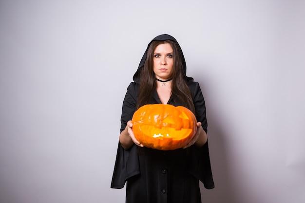 Gotische junge frau im hexenhalloween-kostüm mit einem geschnitzten kürbis auf weißer wand mit kopienraum