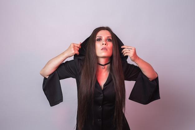 Gotische junge frau im hexenhalloween-kostüm.
