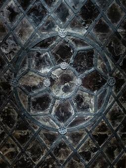 Gotisches gemustertes glasfenster aus geschmiedetem eisenprofil und nieten, gesprungenes glas