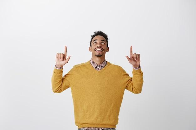 Gott sei dank ist freitag. porträt des erfreuten interessierten jungen afroamerikanischen studenten im stilvollen gelben pullover, der hände hebt, schaut und zeigt und schönen blick auf den himmel genießt