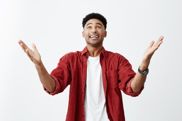 Gott sei dank. nahaufnahme des glücklichen jungen attraktiven schwarzhäutigen mannes mit afro-haarschnitt im lässigen modischen outfit, das hände ausbreitet, glücklich sein, dass er schließlich preis im wettbewerb gewann.