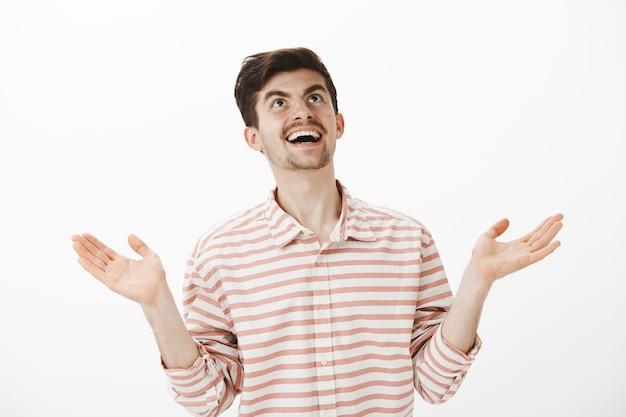 Gott was als nächstes. porträt des sarkastischen lachenden freundes im streifenhemd, die hände hebt und himmel mit lächeln betrachtet, etwas lustiges und interessantes sieht, das gegen graue wand steht