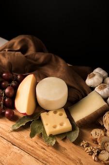 Gouda-, parmesan- und emmentalerkäse mit bestandteilen über holzoberfläche