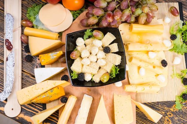 Gourmet-ausstellung verschiedener käsesorten um ein holzbrett herum auf einem buffettisch mit einer zentralen schüssel gefüllt mit käsewürfeln, cocktailzwiebeln und oliven, draufsicht